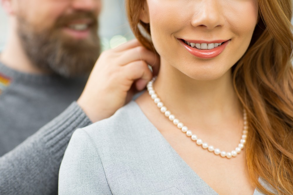 Woman wearing a strand of pearls.