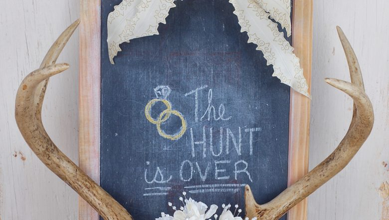 wedding-image-with-antlers-and-silk-flowers-and-ribbons-framing-a-worn-blackboard