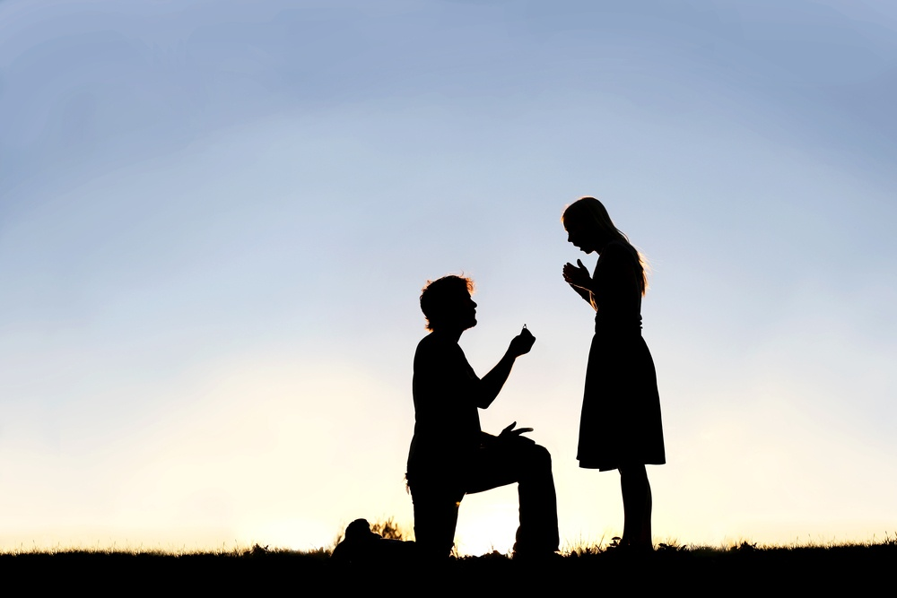 silhouette of a young man down on one knee and holding a diamond engagement ring proposing to his girlfriend