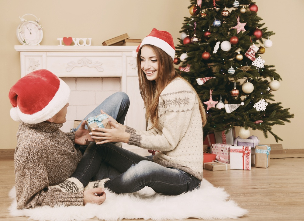 young couple with gifts sitting on carpet at home