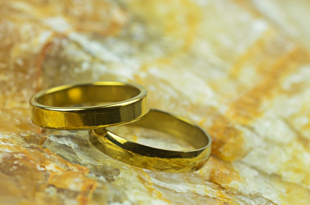 couple gold rings on marble stone