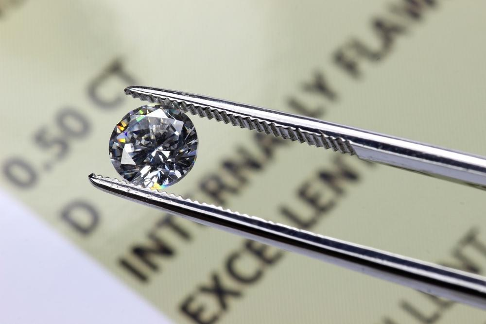 cut diamond held by tweezers above certificate