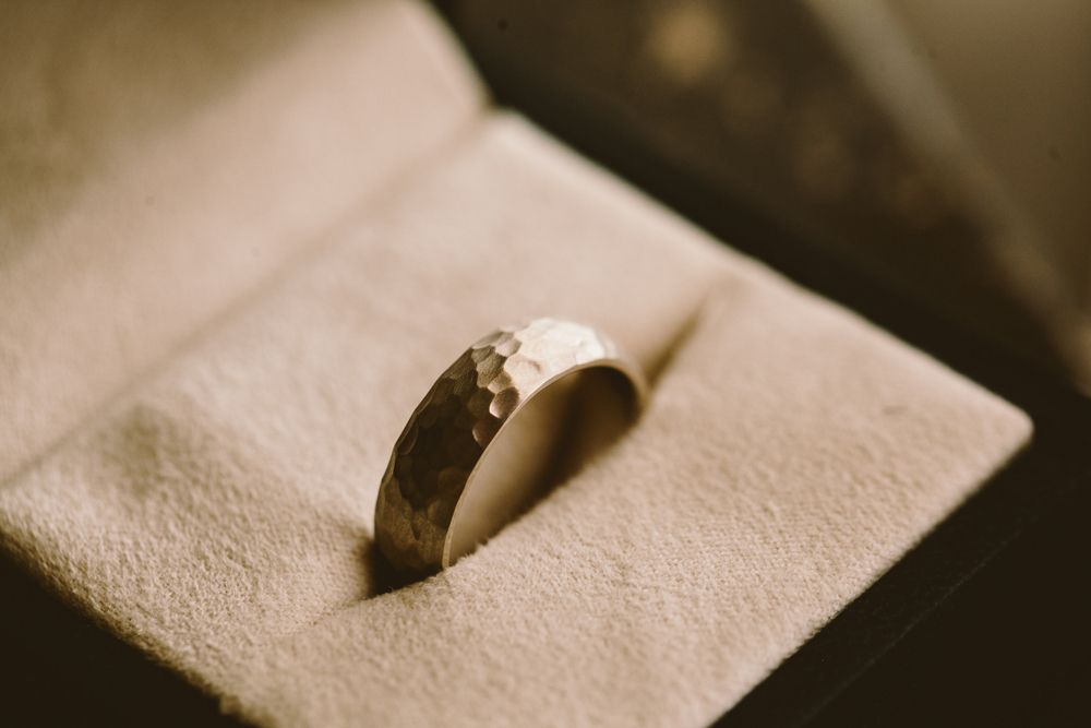 A men's wedding band with a hammered texture