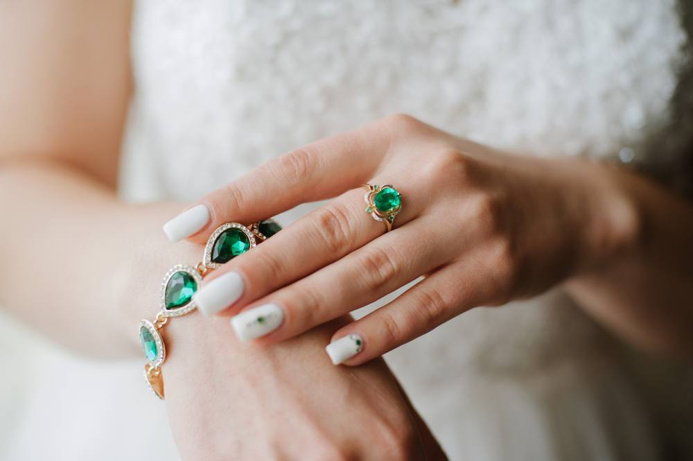 Woman wearing an emerald engagement ring